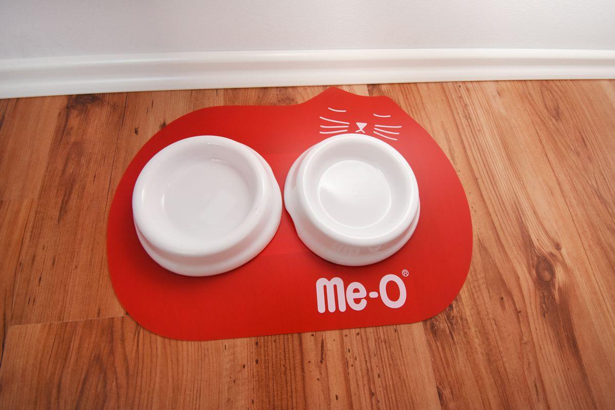 białe miseczki dla kota na czerwonej podkładce