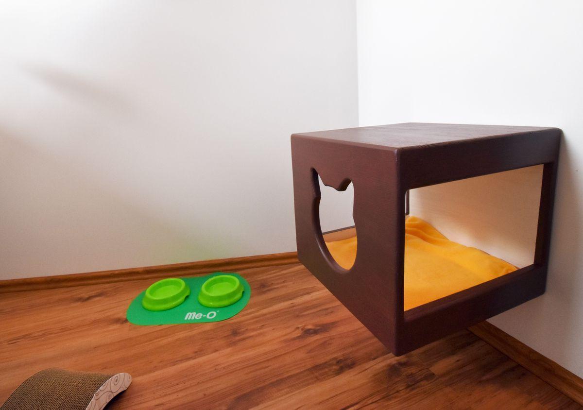 Brązowa budka dla kota i zielone miseczki
